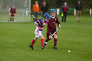 Under 12 school teams boys and girls play the traditional game of Shinty. Kingussie (in red and blue) versus Banavie school from Fort William. Many of the players are sons or daughters of first team players.<br /> <br /> Shinty, or 'Camanachd' in Scottish, is a game only played mostly in the Highlands between teams representing villages and towns. The game is older than the recorded history of Scotland and is played on a grass pitch using a small ball and sticks (called a caman). Each team consists of twelve players and the game is played over two halves of 45 minutes. The the aim is to score goals only by using the caman. A ball hit over the sideline results in a 'shy'. To do a shy a player must throw the ball above his or her head and hit the ball with the caman directly over the head using both hands.