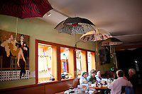 The Drift Inn restaurant in Yachats, Oregon has umbrellas on the ceiling above diners.
