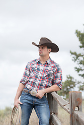 handsome cowboy leaning against a fence on a ranch