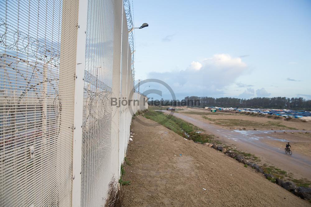 """Calais, Pas-de-Calais, France - 17.10.2016    <br />  <br /> High fences separate the camp from the highway to the port. """"Jungle"""" refugee camp on the outskirts of the French city of Calais. Many thousands of migrants and refugees are waiting in some cases for years in the port city in the hope of being able to cross the English Channel to Britain. French authorities announced that they will shortly evict the camp where currently up to up to 10,000 people live.<br /> <br /> Hohe Zaeune trennen das Camp von der Schnellstraße zum Hafen. """"Jungle"""" Fluechtlingscamp am Rande der franzoesischen Stadt Calais. Viele tausend Migranten und Fluechtlinge harren teilweise seit Jahren in der Hafenstadt aus in der Hoffnung den Aermelkanal nach Großbritannien ueberqueren zu koennen. Die franzoesischen Behoerden kuendigten an, dass sie das Camp, indem derzeit bis zu bis zu 10.000 Menschen leben Kürze raeumen werden. <br /> <br /> Photo: Bjoern Kietzmann"""