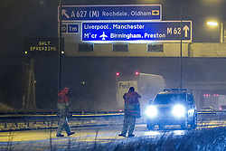 © Licensed to London News Pictures . 23/03/2013 . Rochdale , UK . Motorway police standing in near horizontal sleet block the motorway to vehicles . The M62 motorway closed from Junction 21 Eastbound , at Milnrow , after several lorries became stuck on the freezing roads trying to climb the steep motorway towards Britain's highest motorway peak . The North West Motorway police reported that gritters trying to access the scene to make it safe became stuck too . A car accident also occurred on the Westbound carriageway . Large , stationary traffic queues formed in the closure's wake . Heavy snow and strong winds are creating treacherous driving conditions tonight (22/23rd March 2013) , across the North of England . Photo credit : Joel Goodman/LNP