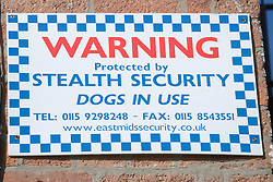 Sign warning that the premises are being protected by a security company that uses dogs,