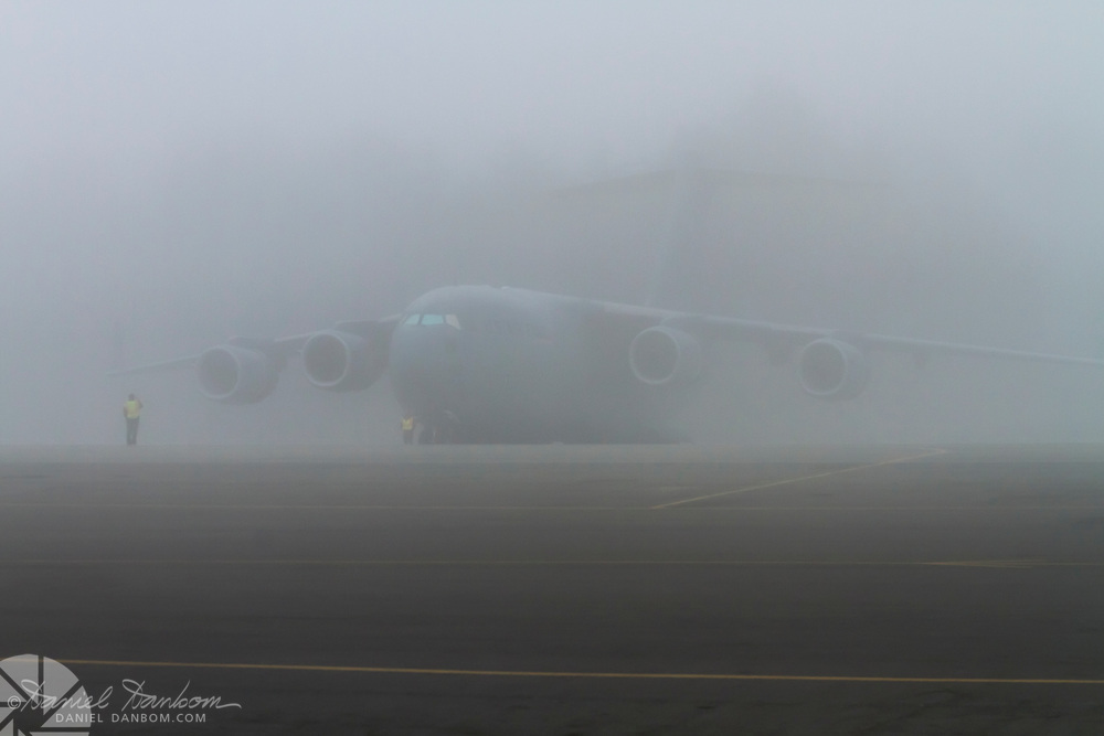 C-17 in the fog, at MRY, Monterey Jet Center, two ramp workers, taking photos with the aircraft