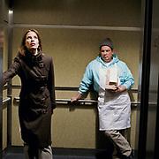 Food deliveryman staring at businesswoman on elevator