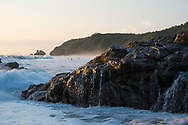 View of the beach at sunset in Mazunte, Mexico. Playa Mermejita, nearly a kilometer long, is the beach behind the rocky outcrop in the foreground.