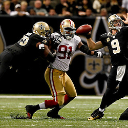 November 25, 2012; New Orleans, LA, USA; New Orleans Saints quarterback Drew Brees (9) is pressured by San Francisco 49ers defensive end Ray McDonald (91) during the second half of a game at the Mercedes-Benz Superdome. The 49ers defeated the Saints 31-21. Mandatory Credit: Derick E. Hingle-US PRESSWIRE