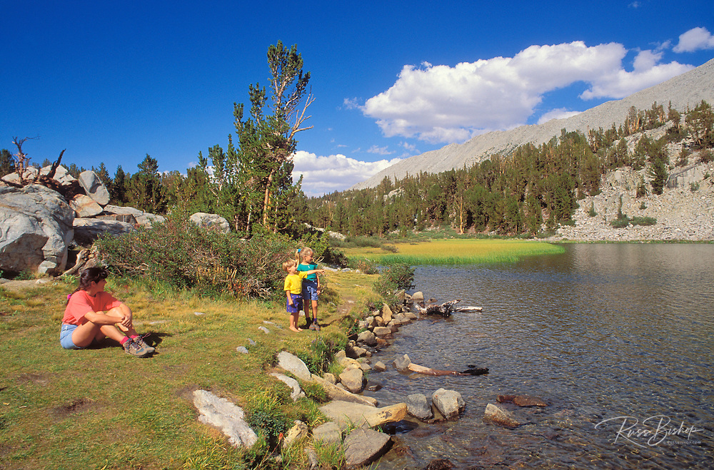 Family relaxing on the shore of Long Lake, John Muir Wilderness, Sierra Nevada Mountains, California