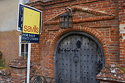 A For Sale sign stands outside the main door of River House, a building in the wool town of Kersey, being sold by the Savills and Winkworth estate agents (both seen on reverse sides of the placard)  that opens on to the street in on 9th July 2020, in Kersey, Suffolk, England. River House is a 15th century Elizabethan town house, on the market for £1.2m though is currently in a derelict state.  The wool trade was already present by the 13th century, steadily expanding as demand grew. By the 1470s Suffolk produced more cloth than any other county.