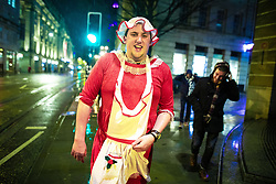 """© Licensed to London News Pictures . 21/12/2018 . Manchester , UK . A man walks along Cross Street wearing a Mrs Claus inspired outfit . Revellers out in Manchester City Centre overnight during """" Mad Friday """" , named for historically being one of the busiest nights of the year for the emergency services in the UK . Photo credit : Joel Goodman/LNP"""