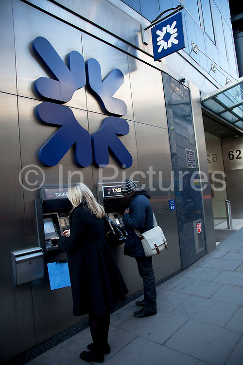 Royal Bank of Scotland cash point ATM machines outside a branch in the City of London. RBS has become a symbol of the recession, credit crunch, financial failure during the economic downturn. Now 80% publicly owned the bank has again been in the news in 2012 following the appointment, then rejection of a 1m pound bonus by it's current chief executive, and the withdrawl of the nighthood of former chief executive.