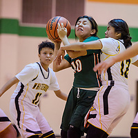 Wingate Bear Dellena Payton (10) is fouled by Whitehorse Raider Nionna Philips (12) Thursday at Wingate High School.
