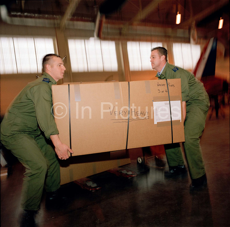 Corporal Andrew Haynes and Senior Aircraftman Michael Owen load boxes packed with the possessions and kit belonging to the elite 'Red Arrows' pilots, Britain's prestigious Royal Air Force aerobatic team, before travelling for winter training at Akrotiri in Cyprus. In the team's hangar at RAF Scampton, Lincolnshire, the two Suppliers lift the reinforced cardboard 'tri-pack' struggling to lift the weight from the ground. Corporal Haynes lifts with the correct technique: knees bent, straight back. The man on the right, has a bent back risking spinal injury. Some 80-plus members of the team will spend six weeks away from home. 23 tons of spares and personal effects travel ahead by ship with another 10 tons travelling on-board a C-130 transport aircraft. The Suppliers ensure possessions and spares are stored taking many weeks of meticulous planning.