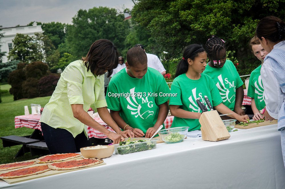 (L-R) Jordan Wilson, Kyla Bourne, Eliza Croom, Rachel Bradley, and Jalen Hurston and  of Sarah Moore Greene Magnet Technology Academy School, Knox County, TN with First Lady Michelle Obama prep vegetables to make pizzas after they harvested the White House Kitchen Garden for the fifth year in a row at the White House on May 28, 2013 in Washington DC. Photo by Kris Connor
