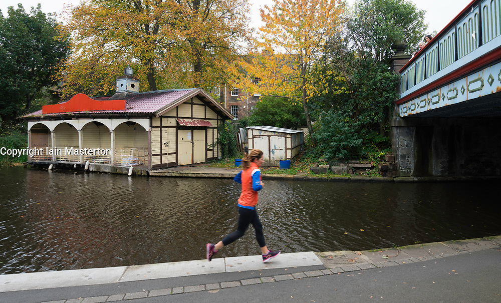 Woman running along towpath beside the Union Canal at Polwarth in Edinburgh, Scotland, United Kingdom.