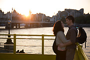 Lovers embrace at sunset on the yellow gantry walkway which joins a terrace to the main walkway on the Southbank, London, UK. The South Bank is a significant arts and entertainment district, and home to an endless list of activities for Londoners, visitors and tourists alike.