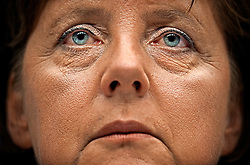 German Chancellor, Angela Merkel listens during a late night press conference at the end of a marathon session, of the EU Summit in Brussels. (Photo © Jock Fistick)