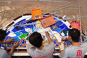 Employees assemble a stained glass window at the Eztu Glass factory in Tangerang, near Jakarta, Indonesia, on July 2, 2015.