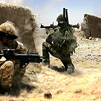10th July 2007.Kajaki, Helmand Province, Afghanistan..An Afghan soldier fires a Rocket Propelled Grenade at a Taliban position, a British officer crouches in cover and protects his ears from the blast during operations against the Taliban in the Kajaki district of Helmand Province, Afghanistan on the 10th July 2007. After a long day of skirmishes with the Taliban an air strike was called on a compound thought to contain an enemy firing position. After the explosions the British and Afghan troops moved into the destroyed compound where they found 3 dead fighters and captured 2 more who were trapped in their collapsed bunker. The captured men both received medical treatment from the British and were given water by the Afghan soldiers they had been fighting only minutes before. A number of weapons were captured including Kalashnikov assault rifles, rocket propelled grenade launchers and war heads and a belt fed machine gun. The soldiers of 1 Royal Anglian have been fighting the Taliban in the area for more than 3 months; this constitutes their most successful capture of weapons and enemy fighters.