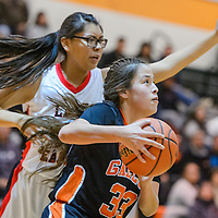 Gallup JV Bengal Samantha Quigley (33) frushes past  Crownpoint Eagle Rodera Johnson (31) Friday at Wingate High School.