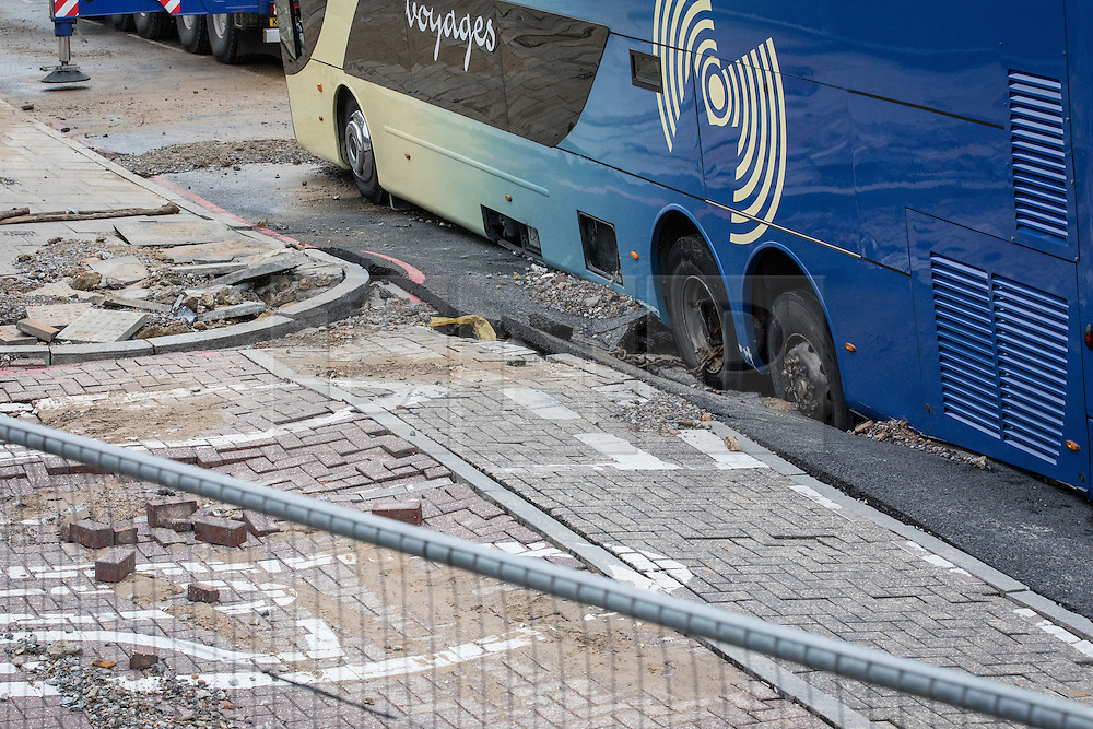 © Licensed to London News Pictures. 27/11/2016. London, UK. The wheels of a French tourist coach which fell into a sinkhole in Lewisham. Lee High Road has been closed off and police declared a 'major incident' after the coach with 100 passengers on board fell into a sinkhole caused by a burst water mains, flooding a long stretch of the road including many local businesses. . Photo credit: Rob Pinney/LNP