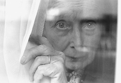 Elderly woman standing at window looking through curtains,