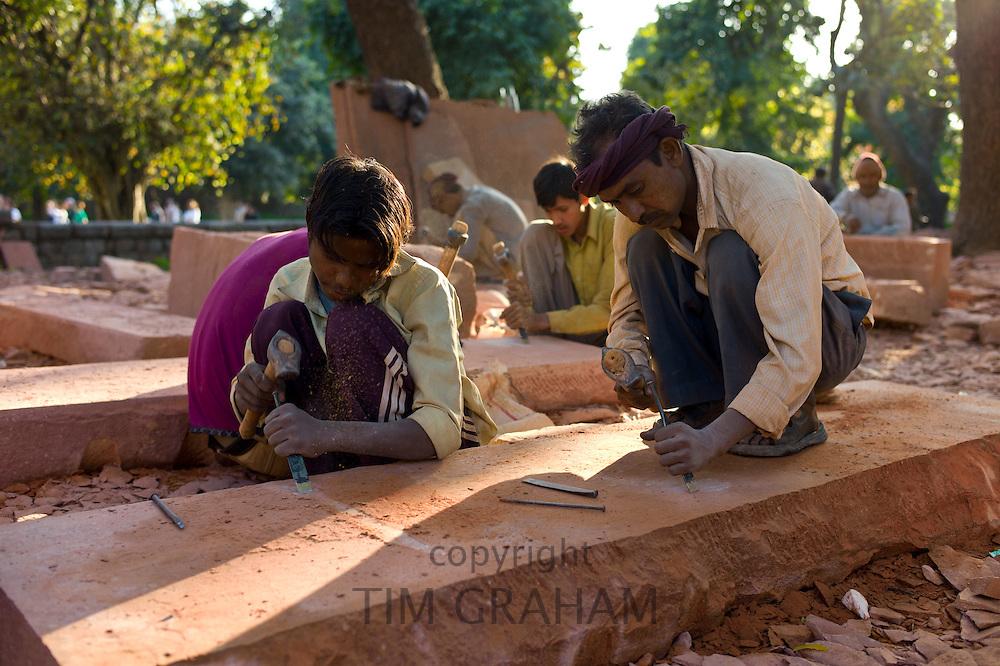 Stonemasons using traditional manual skills at stone workshop at Humayuns Tomb,  in New Delhi, India