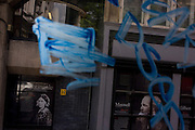 Faces of eminent achievers of UCL university seen through blue graffiti on a bus in central London.