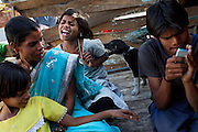 Poonam, 10, (centre) is being bitten on the arm by a stray puppy taken from the streets of Oriya Basti, one of the water-contaminated colonies in Bhopal, central India, near the abandoned Union Carbide (now DOW Chemical) industrial complex, site of the infamous '1984 Gas Disaster'. Sachin, 18, (right) Poonam's disabled, oldest brother, a boy affected by a lower limbs paralysis, is playing games on a cellphone, while (right) Jyoti, 11, Poonam's sister, and Sangita Jatev, 39, their mother, are sitting in the front yard of their newly built home.