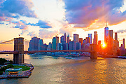New York skyline at sunset under dramatic sky, featuring the Financial District of Manhattan, the Brooklyn Bridge and the East River, New York City.