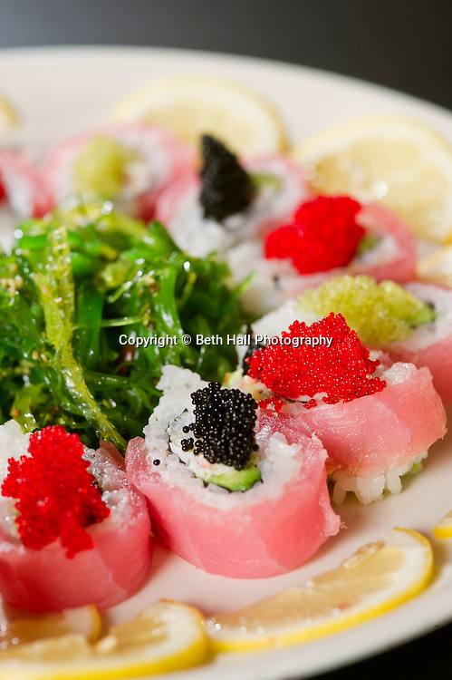 A sushi roll with roe and a seaweed salad and lemon slices.