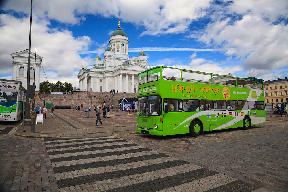 A sightseeing bus on Senate Square in Helsinki, Finland. Over three million tourists visit Helsinki every year.