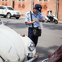A traffic cop writes a parking ticket for a Volkswagen Beetle in Ho Chi Minh City, Vietnam.