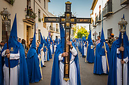 """Every holy week procession begins with a hooded man carrying a big cross. A line that for the biggest brotherhoods can be formed by thousands of """"nazarenos"""" follows the cross. Cordoba, Spain."""