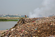 A man searches through a burning rubbish pile on the banks of the Turag river on the 1st of October 2018 in Dhaka, Bangladesh. Environmental pollution next to rivers and lakes is a common sight in Dhaka, polluting water sources that also used for washing and drinking water.  (photo by Andrew Aitchison / In pictures via Getty Images)