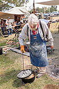 An old cowboy cook prepares biscuits using an iron pot during a chuck wagon competition during Cheyenne Frontier Days July 25, 2015 in Cheyenne, Wyoming. Frontier Days celebrates the cowboy traditions of the west with a rodeo, parade and fair.