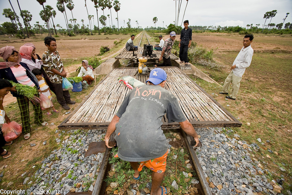 """01 JULY 2006 - PHNOM PENH, CAMBODIA: Train drivers put together a bamboo train in central Cambodia. The """"bamboo trains"""" run along the government tracks in rural Cambodia. Bamboo mats are fitted over wheels which ride on the rails. The contraption is powered by a either a motorcycle or lawn mower engine. When two bamboo trains meet, the lighter train is taken apart to allow the heavier one to pass. Both drivers take apart and put together the train. The Cambodian government would like to get rid of the bamboo trains, but with only passenger train in the country, that runs only one day a week, the bamboo trains meet a need the government trains do not. While much of Cambodia's infrastructure has been rebuilt since the wars which tore the country apart in the late 1980s, the train system is still in disrepair. There is now only one passenger train in the country. It runs from Phnom Penh to the provincial capitol Battambang and it runs only one day a week. It takes 12 hours to complete the 190 mile journey.  Photo by Jack Kurtz / ZUMA Press"""