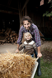 Father with his son pushing wheelbarrow in the farm, Bavaria, Germany