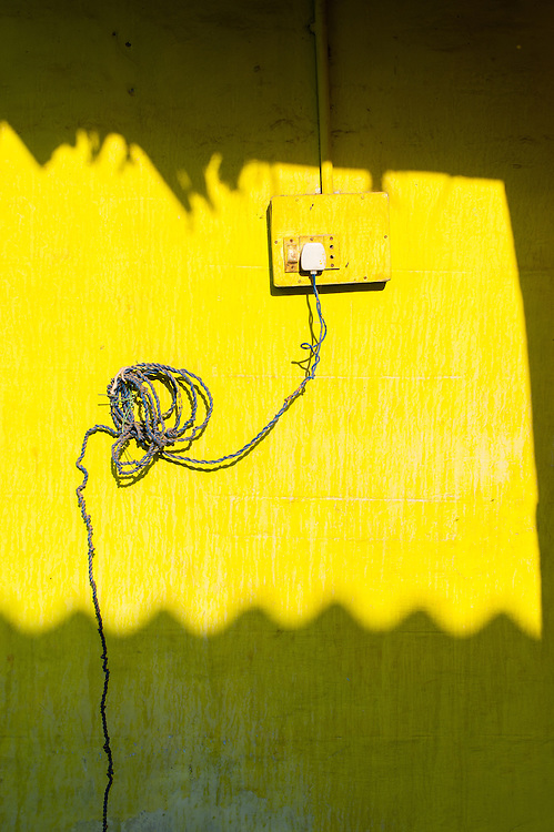 Electric wire, plug and socket on yellow wall