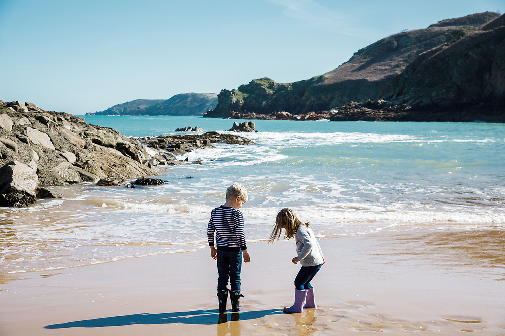Boy and girl playing in the sand in their wellies on the shoreline of Greve de L'Ecq beach, Jersey, Channel Islands