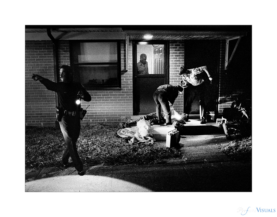 Shooting<br /> <br /> A Greensboro police officer takes charge as paramedics assist Kevin Barrett of Greensboro who was found shot on the back porch of an apartment. Barrett was in critical condition after being shot five times in an apparent drug related altercation.<br /> <br /> Published October 1988<br /> News & Record