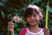 An Indonesian child (8-year-old Ni Wayan Sriyani) displays the fruits of her hunt in a rice paddy (captured dragonflies) to be fried later in coconut oil and eaten like candy, Batuan, Bali, Indonesia.(Man Eating Bugs page 58,59)