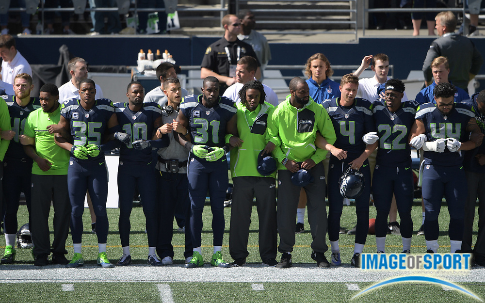 Sep 11, 2016; Seattle, WA, USA; Seattle Seahawks players and coaches interlock elbows during the playing of the national anthem during a NFL game against the Miami Dolphins at CenturyLink Field.