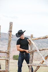 rugged cowboy closing a rustic gate on a ranch