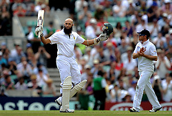 South Africa's Hashim Amla raises his bat to the crowd after reaching a century against England.