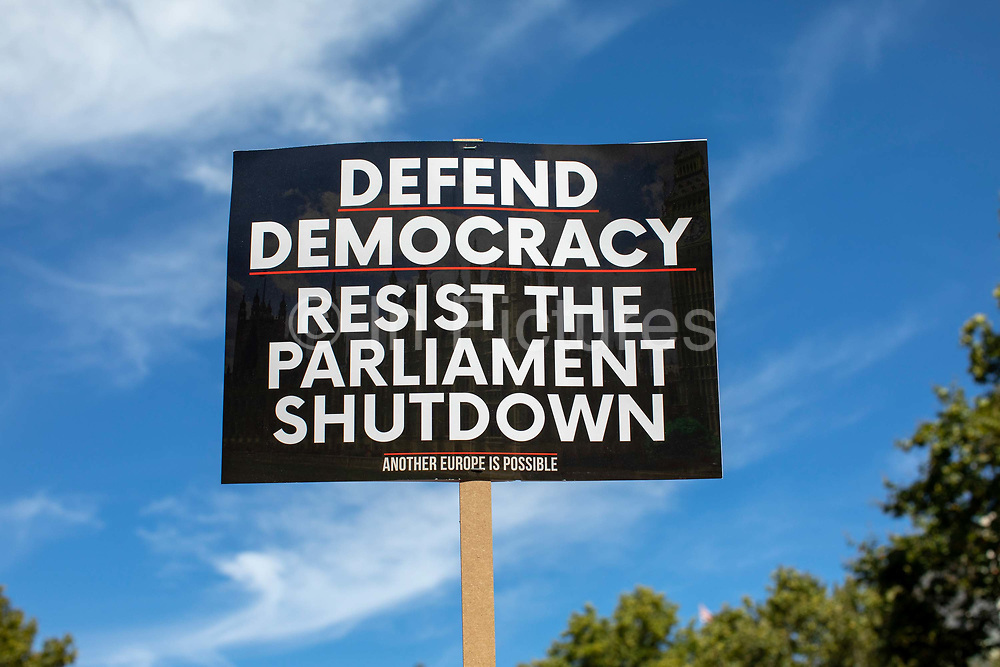 A Defend Democracy placard during the Stop The Coup protest against the proroguing of Parliament on 31st August 2019 in London in the United Kingdom. Left-wing group Momentum and the Peoples Assembly coordinated a series of Stop The Coup protests across the UK today, aimed at Boris Johnson and the UK government proroguing Parliament.