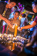 28 NOVEMBER 2012 - BANGKOK, THAILAND: A family lights the candles on their krathongs before floating them in a small pool at Wat Yannawa in Bangkok. Loy Krathong takes place on the evening of the full moon of the 12th month in the traditional Thai lunar calendar. In the western calendar this usually falls in November. Loy means 'to float', while krathong refers to the usually lotus-shaped container which floats on the water. Traditional krathongs are made of the layers of the trunk of a banana tree or a spider lily plant. Now, many people use krathongs of baked bread which disintegrate in the water and feed the fish. A krathong is decorated with elaborately folded banana leaves, incense sticks, and a candle. A small coin is sometimes included as an offering to the river spirits. On the night of the full moon, Thais launch their krathong on a river, canal or a pond, making a wish as they do so.    PHOTO BY JACK KURTZ