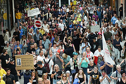 © Licensed to London News Pictures. 24/07/2021. Manchester, UK. Protesters hold banners and shout slogans as they storm Arndale shopping centre in Manchester during an anti-lockdown protest. Photo credit: Ioannis Alexopoulos/LNP