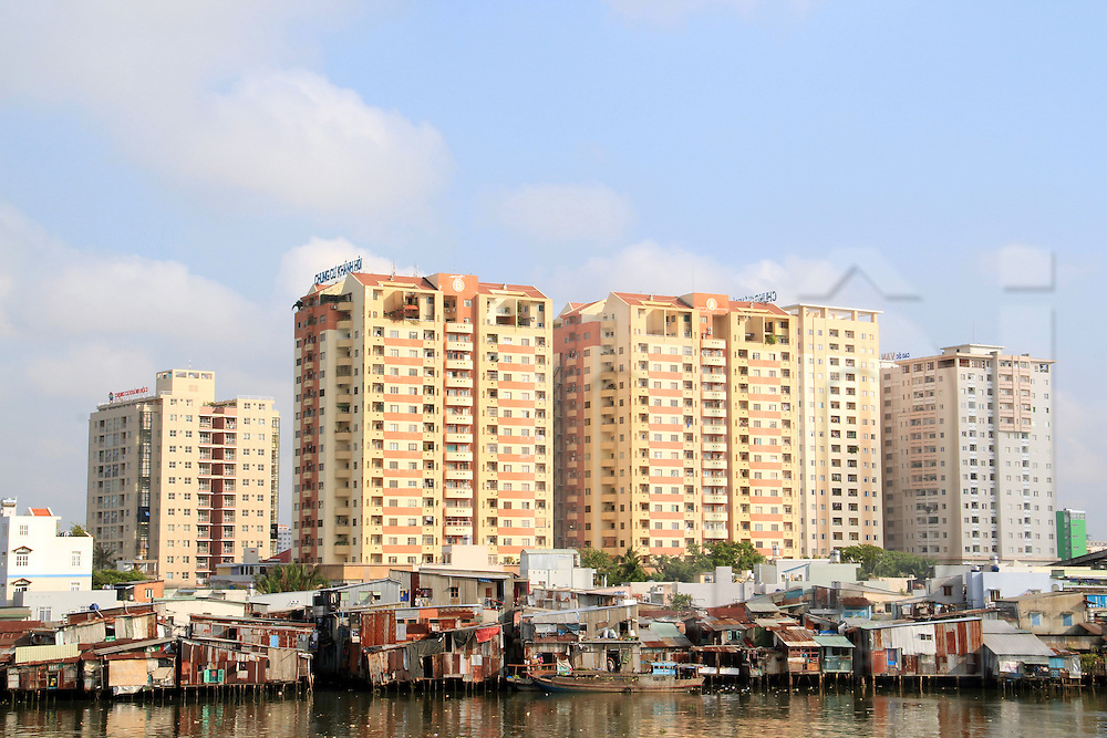 Modern buildings raise to sky and contrast with shantytowns along Doi channel (kenh doi) in district 8, Ho Chi Minh city, Vietnam,  Asia