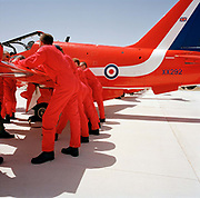 Officer pilots of the elite 'Red Arrows', Britain's prestigious Royal Air Force aerobatic team, lean against a wing of their Hawk jet in a pre-flight briefing while a member of their ground crew positions some wheel chocks. It is mid-day and the officers are deep in conversation with the RAF roundel emblem is on the jet aircraft. The better-educated officers in the armed forces enjoy a more privileged lifestyle than their support staff. In the aerobatic squadron, the Blues outnumber the pilots 8:1. Without them, the Red Arrows couldn't fly. Some of the team's Hawks are 25 years old and their air frames require constant attention, with increasingly frequent major overhauls due.