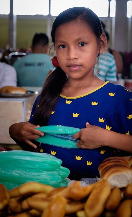 NAUTA, PERU - CIRCA OCTOBER 2015:  Girl selling bread in Nauta market in the Peruvian Amazon